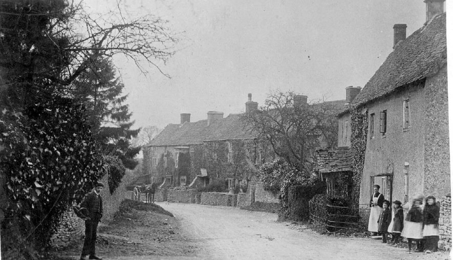 Part of village street with cottages, horse and trap, errand boy and group of children with woman, Cherington.  1900s |  IMAGE LOCATION: (Warwickshire County Record Office)
