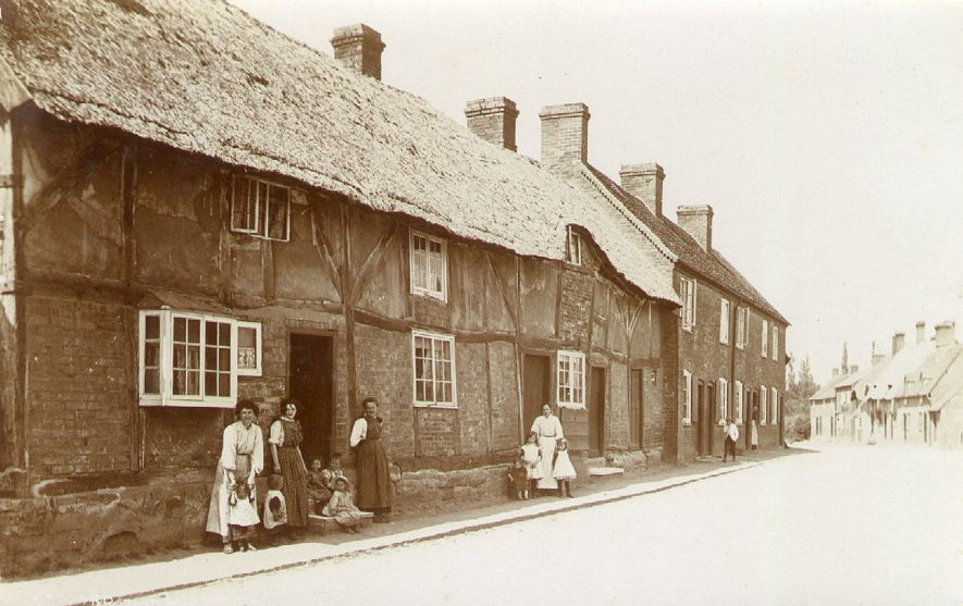 Village street with thatched cottages showing women and children at doorways, Radford Semele.  1900s |  IMAGE LOCATION: (Warwickshire County Record Office)