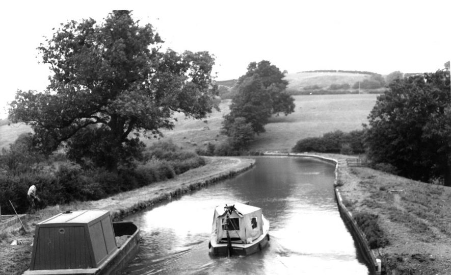 The Oxford Canal, near Napton on the Hill; with small canal cruiser and small maintenance boat.  1960s [Taken from the canal bridge looking north towards the Windmill. The location is Napton Bottom lock, commonly known as the Folly which was the former location of the Public house called the Bull and Butcher.][The man working on the left hand towpath is most likely Esme Dowling, employed by British Waterways at Napton. The photograph was most likely taken from the Folly Bridge No.113 at Napton Bottom Lock looking north.] |  IMAGE LOCATION: (Warwickshire County Record Office)