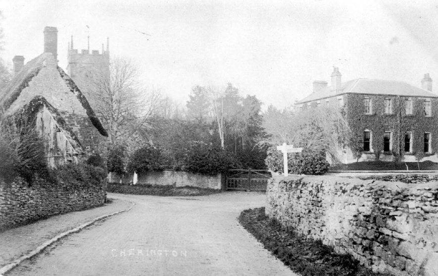 Junction of village streets with signpost showing the church tower, cottages and large house, Cherington.  1900s |  IMAGE LOCATION: (Warwickshire County Record Office)