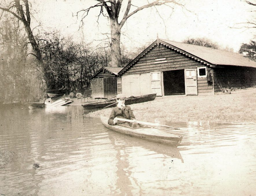 The Warwick boat house on the River Avon, Warwick. A boy is in a canoe type boat on the river.  1900s |  IMAGE LOCATION: (Warwickshire County Record Office)