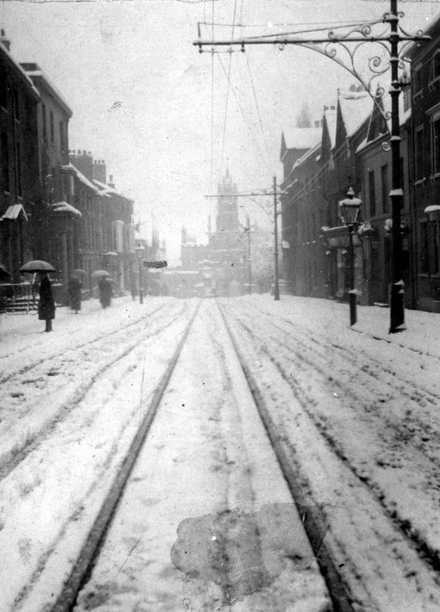 Jury Street, looking towards Eastgate, Warwick, with snow on the ground and people with umbrellas on the pavement.  1900s |  IMAGE LOCATION: (Warwickshire County Record Office)