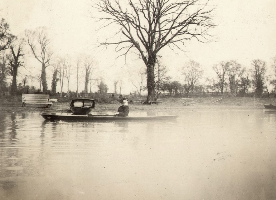 A man sitting in a boat on the River Avon at Warwick. Warwick boat club grounds are in the background.  1910s |  IMAGE LOCATION: (Warwickshire County Record Office)