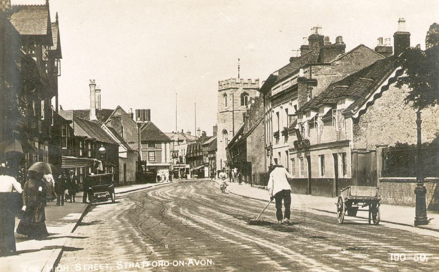 Church Street, Stratford upon Avon [labelled High Street on postcard]. A man with his handcart is sweeping the road and a car is parked on the left. 1910s |  IMAGE LOCATION: (Warwickshire County Record Office)