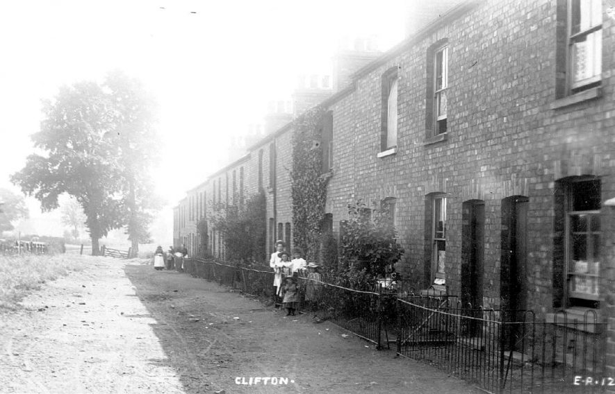 Road with terrace houses on one side only, possibly known as Avon Street. Women and children standing in front of the houses. Gate leading to field in background.  Clifton upon Dunsmore.  1900s |  IMAGE LOCATION: (Warwickshire County Record Office)