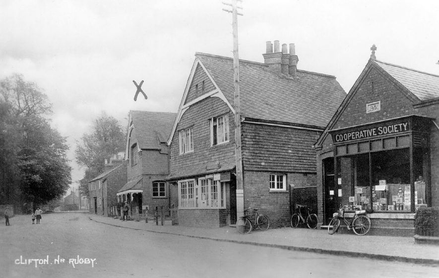 Village street with the Village Hall, known as The Townsend Memorial Hall and Co-operative Stores with the post office between.  Clifton upon Dunsmore.  1930s |  IMAGE LOCATION: (Warwickshire County Record Office)