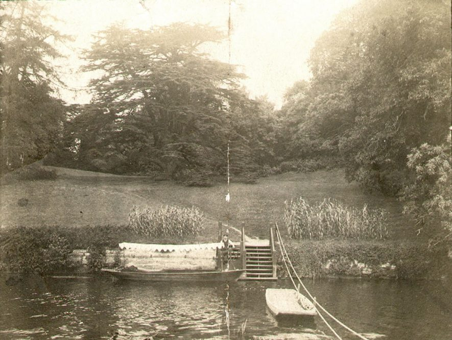 Electrically powered boat moored by Warwick Castle grounds. Samuel Bissell in boat.  1910s |  IMAGE LOCATION: (Warwickshire County Record Office)