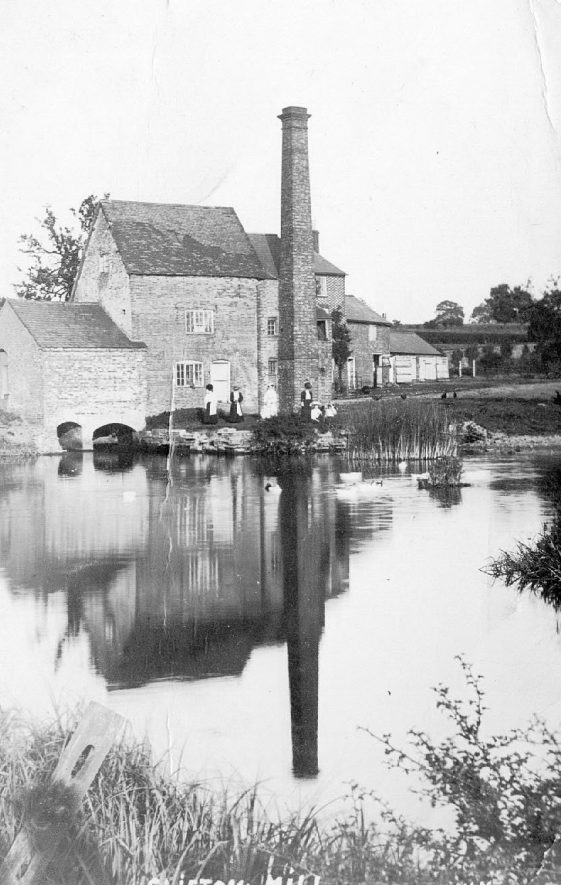 Clifton upon Dunsmore Mill with chimney and millpond in front.  1900s |  IMAGE LOCATION: (Warwickshire County Record Office)