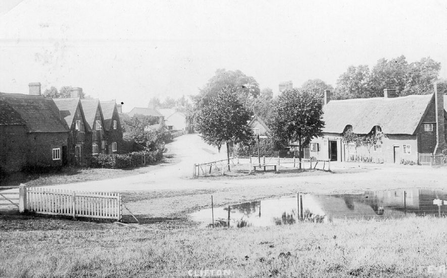 Junction of Lilbourne Road with Hillmorton Lane, Clifton upon Dunsmore, forking off to the left. The village blacksmiths is in one of the cottages to the right, and the village pond is in the foreground.  1920s |  IMAGE LOCATION: (Warwickshire County Record Office)