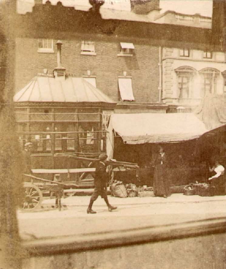 Market stall and shops in Market Place, Rugby.  1890s |  IMAGE LOCATION: (Warwickshire County Record Office)