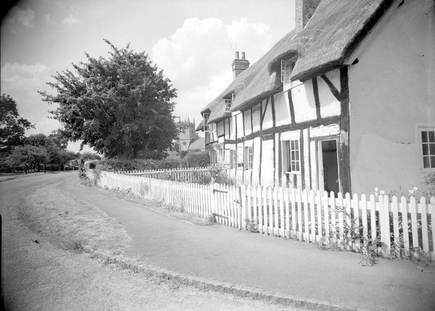 Thatched and timbered cottages with St Helen's church in the background, Clifford Chambers.  July 1st 1957 |  IMAGE LOCATION: (Warwickshire County Record Office)
