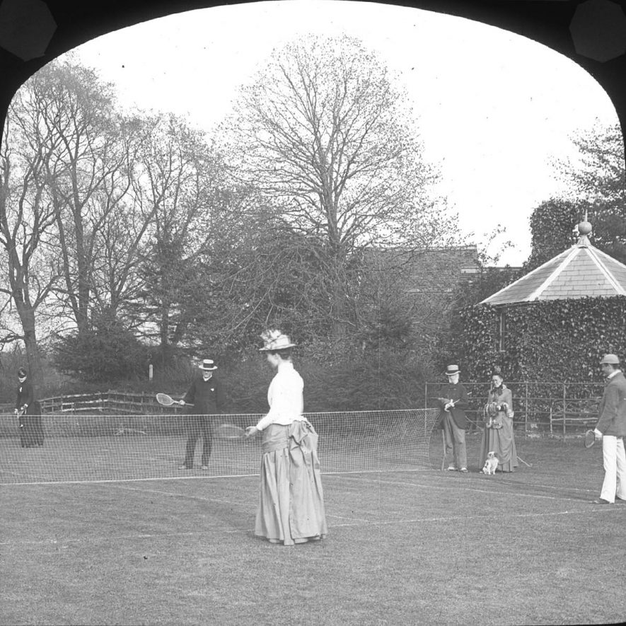 Lady and gentleman playing tennis on lawn.  Onlookers.  Clifford Chambers.  1900 |  IMAGE LOCATION: (Warwickshire County Record Office)