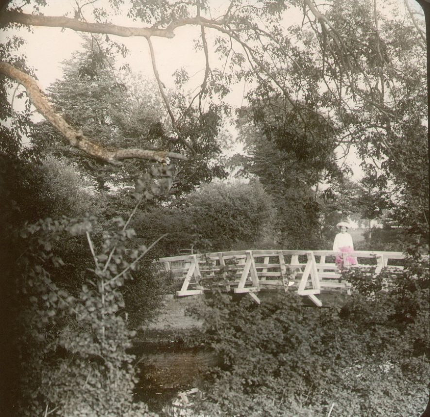 Lady sitting on a footbridge over the River Stour at Clifford Chambers.  1900s |  IMAGE LOCATION: (Warwickshire County Record Office)