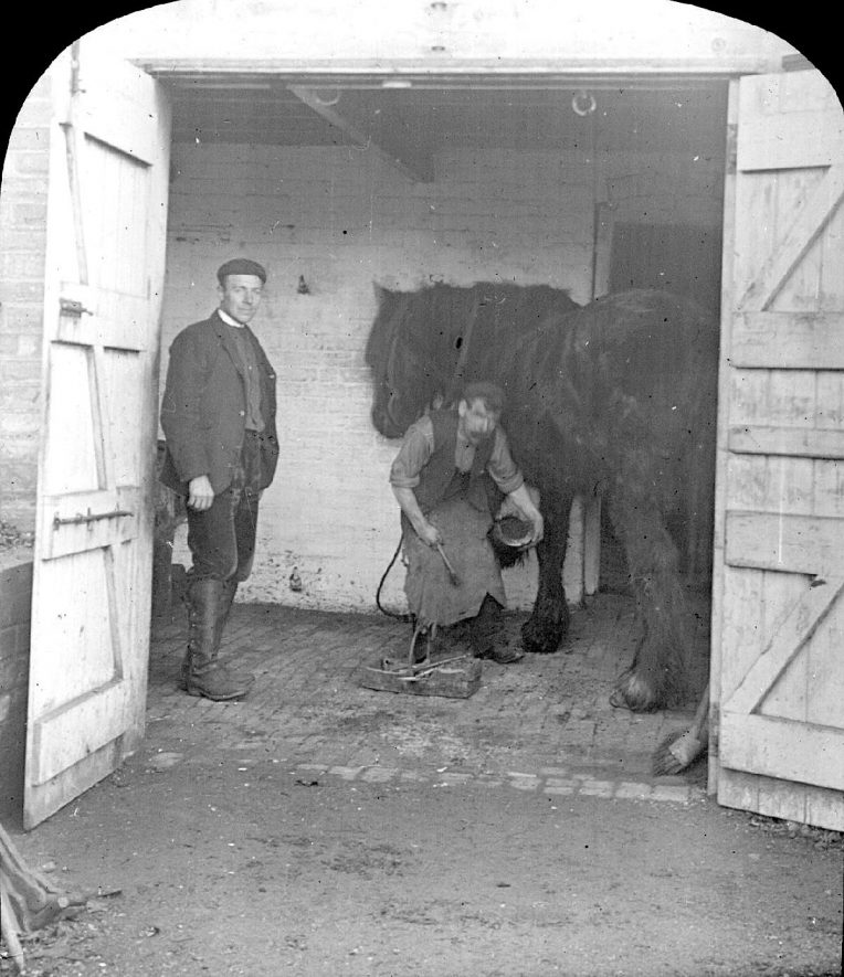 Seth Smith and Mr Weaving shoeing a horse in Clifford Chambers.  1900s |  IMAGE LOCATION: (Warwickshire County Record Office) PEOPLE IN PHOTO: Weaving, Mr, Weaving as a surname, Smith, Seth, Smith as a surname