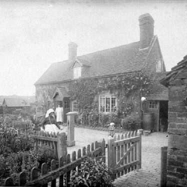 Cubbington.  Mrs Wells in front of her cottage