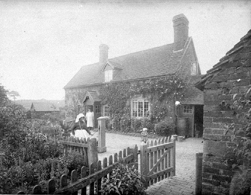 Mrs Wells at water pump in front garden of cottage.  1904 |  IMAGE LOCATION: (Warwickshire County Record Office) PEOPLE IN PHOTO: Wells, Mrs