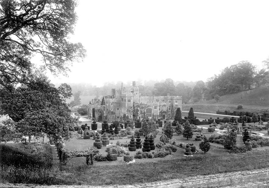 Compton Wynyates house and gardens. Two gardeners are seen among the topiary trees.  1900s |  IMAGE LOCATION: (Warwickshire County Record Office)