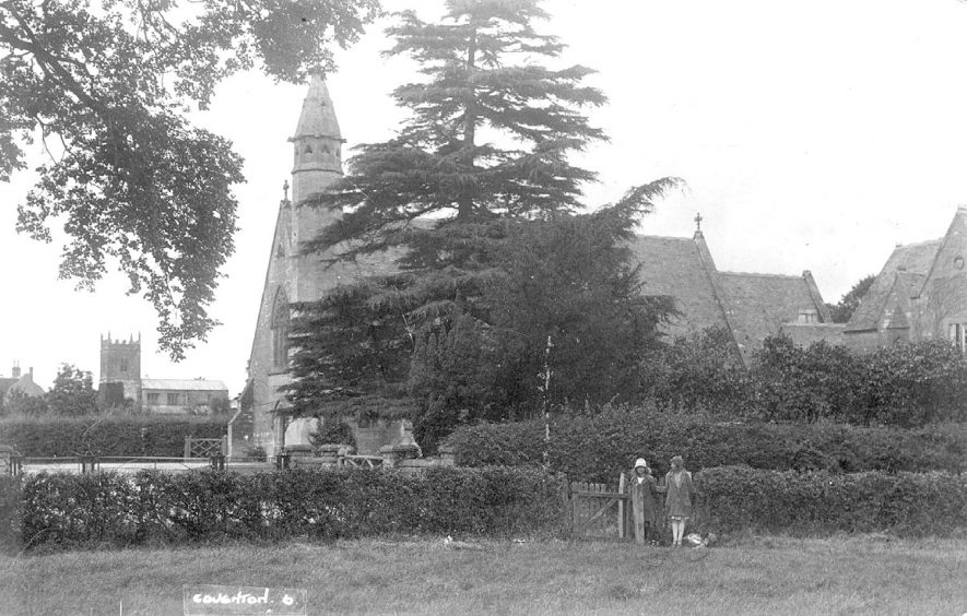 The catholic church of Saints Peter, Paul and Elizabeth at Coughton. The Church of England church of St Peter can be seen in the background. Two girls are seen standing by a gate.  1920s |  IMAGE LOCATION: (Warwickshire County Record Office)