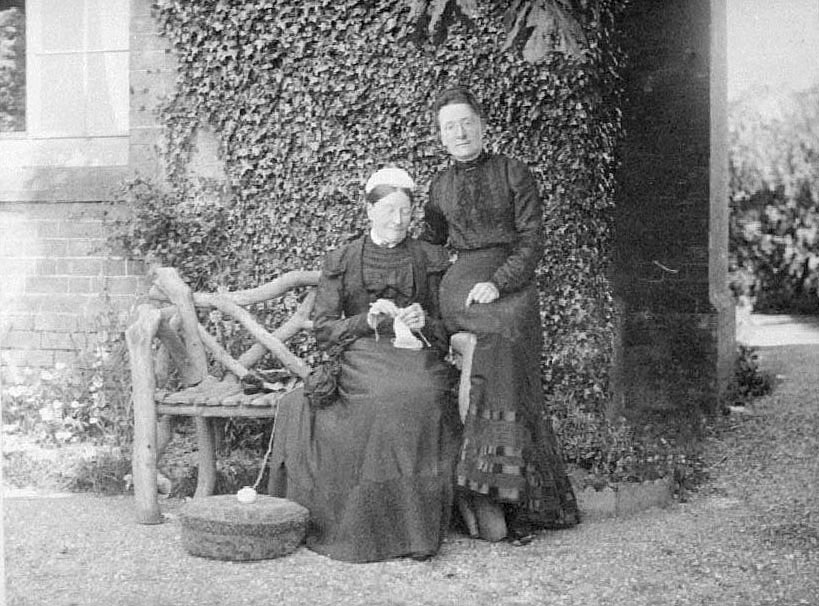 Two ladies of Cubbington sitting on rustic garden seat, one with knitting.  1904 |  IMAGE LOCATION: (Warwickshire County Record Office)