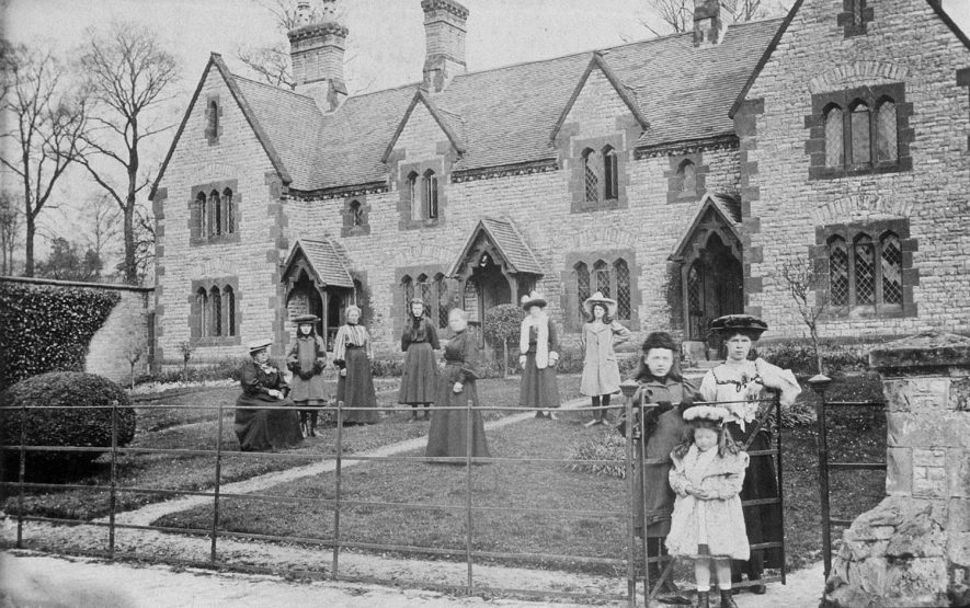 A group of women and children, standing in front of cottages in Combrook.  1910s |  IMAGE LOCATION: (Warwickshire County Record Office)