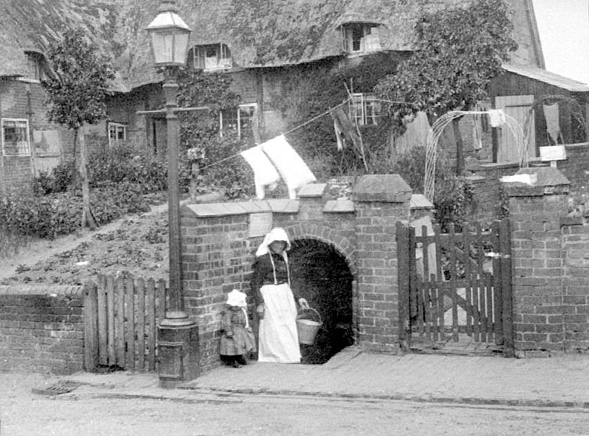 Mrs Wells and child at village well in Queen Street, Cubbington.  1904 |  IMAGE LOCATION: (Warwickshire County Record Office) PEOPLE IN PHOTO: Wells, Mrs