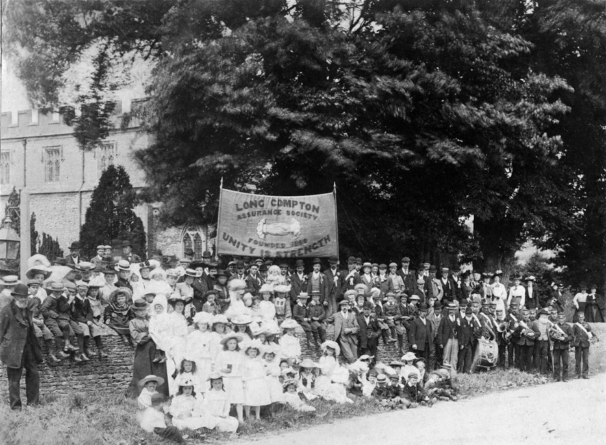 Gathering of the members of Long Compton Assurance Society in front of the church. They are holding a large banner aloft.  c.1904 |  IMAGE LOCATION: (Warwickshire County Record Office) IMAGE DATE: (c.1904)