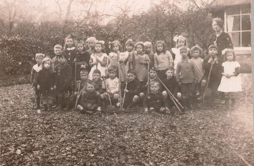 Studley Council School class II and part of class I in a gardening lesson.[Denis Charles Spiers, of Holt Road,Studley, is seated on the left end of the row of seated children, holding a hoe.He was born in 1913.]  1921 |  IMAGE LOCATION: (Warwickshire County Record Office)