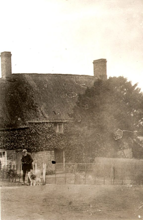 The Orchards, Lower Tysoe, cottage lived in by the Ashbys.  Man with dog.  1900s |  IMAGE LOCATION: (Warwickshire County Record Office)