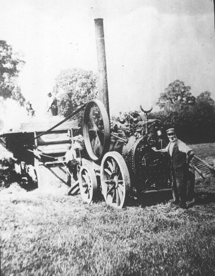 Mobile steam engine and threshing machine with driver in front.  1900s |  IMAGE LOCATION: (Warwickshire County Record Office)