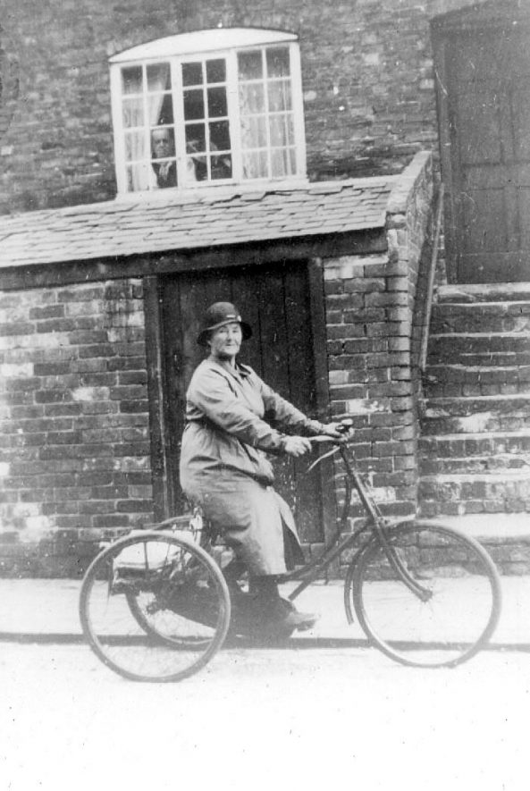 Mrs Mary Bastock, Cubbington newsagent, delivering newspapers on her tricycle. She lived to be 100 years old and her son, Ted also ran the village paper shop for many years.  1930s |  IMAGE LOCATION: (Warwickshire County Record Office) PEOPLE IN PHOTO: Bastock, Mary, Bastock as a surname