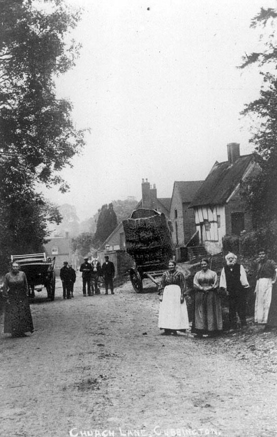 Church Lane, Cubbington, showing group of people, cottages and farm wagons.  1900s |  IMAGE LOCATION: (Warwickshire County Record Office)