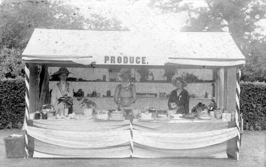 Three ladies manning the produce stall in the grounds of Red Hill House, Clifford Chambers.  1900s |  IMAGE LOCATION: (Warwickshire County Record Office)