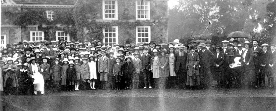 Large gathering of people in front of The Manor House, Clifford Chambers. Mrs Rees-Mogg is seated to the left.  1920s    IMAGE LOCATION: (Warwickshire County Record Office) PEOPLE IN PHOTO: Rees-Mogg, Mrs, Rees-Mogg as a surname