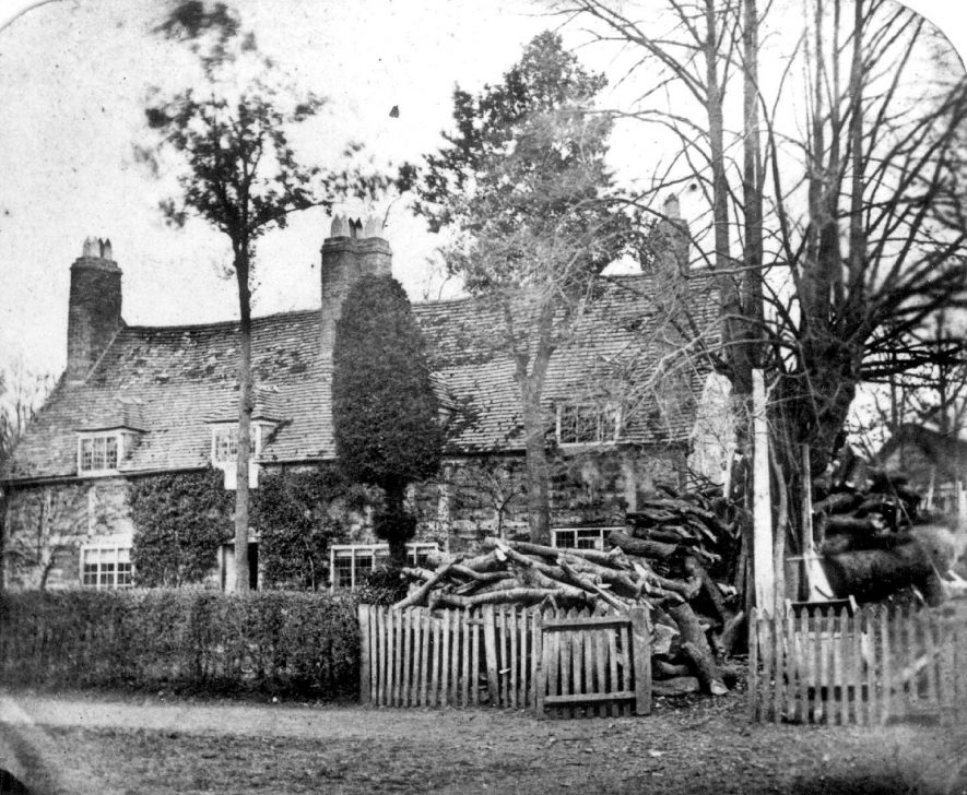 The Hollies, Clifford Chambers. This half timbered Elizabethan cottage opposite the church has been used for various purposes as well as a homestead. This photograph shows it when it was used as a sawmill in the latter part of the last century. At the same time it was also a sweet shop and grocers.  1890s |  IMAGE LOCATION: (Warwickshire County Record Office)