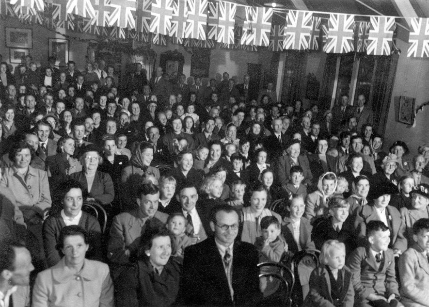 A large audience watching a concert in the Jubilee Hall, Clifford Chambers, on Coronation Day.  June 1953 |  IMAGE LOCATION: (Warwickshire County Record Office)