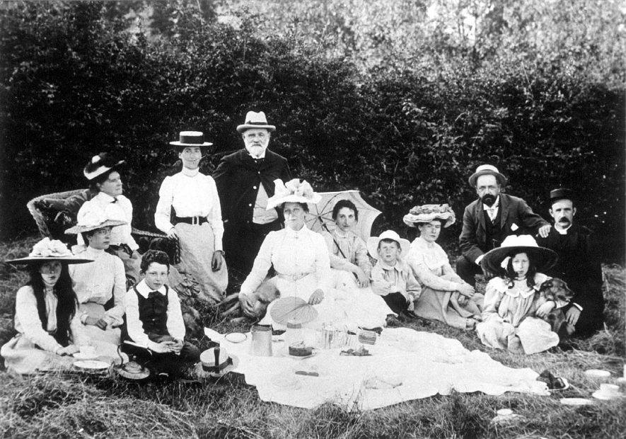 A family picnic at Lower Brailes. The boy seated at the front is Marshall Findlay, the girl on the right with the dog is Miss Garrard, the man on the extreme right is the Rev. Garrard, next to him is Dr. Findlay, the small boy next to the lady with the parasol is Geoffrey Garrard, the lady with the parasol is Mrs Garrard (nee Smith), next to her, holding the fan is Mrs Smith[nee Mary Anne Jane Jordan], and standing at the back is the Rev.[Thomas] Smith.  1900s |  IMAGE LOCATION: (Warwickshire County Record Office) PEOPLE IN PHOTO: Smith, Revd Thomas, Smith, Mrs Thomas, Smith as a surname, Garrard, Revd F E, Garrard, Mrs, Garrard, Miss, Garrard Geoffrey, Garrard as a surname, Findlay, Marshall, Findlay, Dr, Findlay as a surname