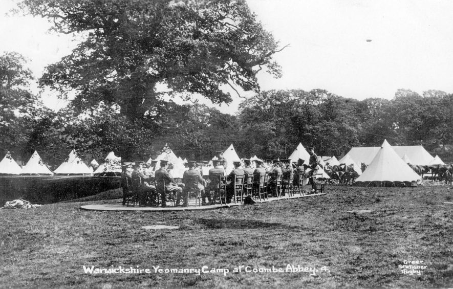 Warwickshire Yeomanry camp at Coombe Abbey.  Bell tents. Soldiers seated in circle, playing brass instruments.  1910s |  IMAGE LOCATION: (Warwickshire County Record Office)