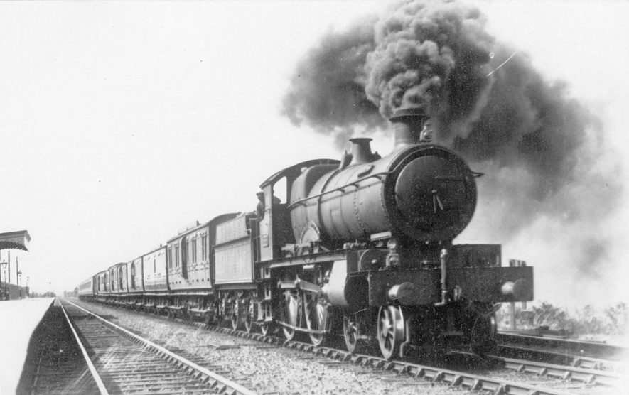 A steam train passing through Fenny Compton station.  1920s