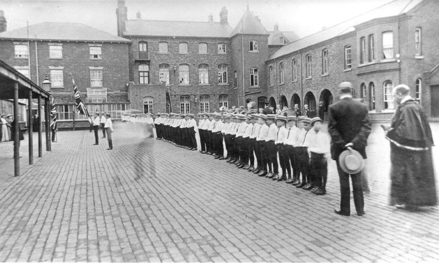 Inspection of boys in the yard at the Shawbury Industrial school, Fillongley.  1910s |  IMAGE LOCATION: (Warwickshire County Record Office)