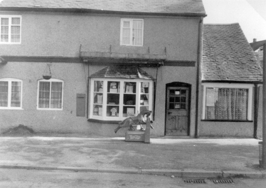 The post office at Fillongley. A coin in the slot rocking horse is standing in front of the window.  1975 |  IMAGE LOCATION: (Warwickshire County Record Office)