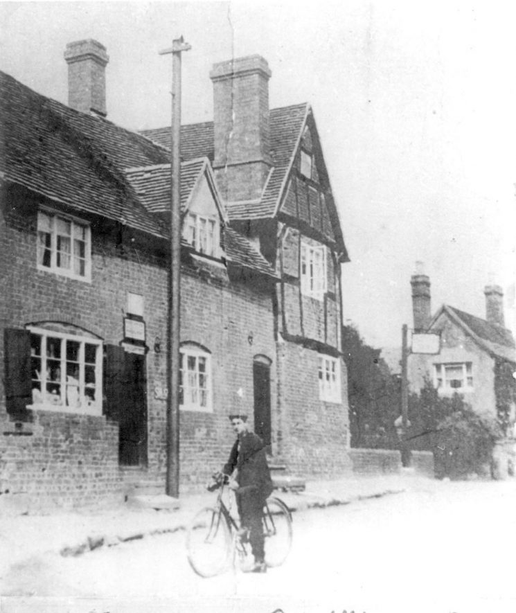 The post office at Fillongley. A man is standing in the road with his bicycle.  1930s |  IMAGE LOCATION: (Warwickshire County Record Office)