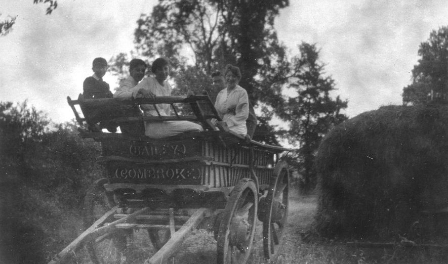 A farm wagon with women and a boy sitting on top, Combrook.  1920s |  IMAGE LOCATION: (Warwickshire County Record Office)