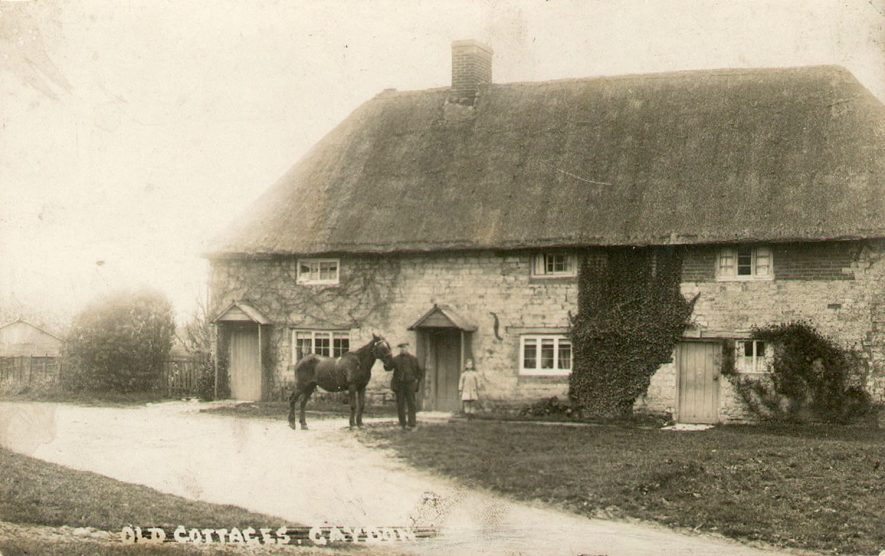Old thatched cottages in Gaydon. A man is standing in front with a horse.  1900s |  IMAGE LOCATION: (Warwickshire County Record Office)