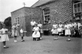 Group of children outside the school in Gaydon. They are dressed up possibly for May Day celebrations.  1959 |  IMAGE LOCATION: (Warwickshire County Record Office)