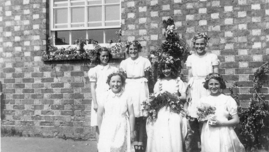 Group of school children dressed up possibly for May Day celebrations at Gaydon School.  Back row, left to right: Susan Coxon, Ann Kitchen, Elizabeth Coxon. Front row: Rosemary Garratt and two unnamed.  1956 |  IMAGE LOCATION: (Warwickshire County Record Office) PEOPLE IN PHOTO: Kitchen, Ann, Kitchen as a surname, Garratt, Rosemary, Garratt as a surname, Coxon, Susan, Coxon, Elizabeth, Coxon as a surname