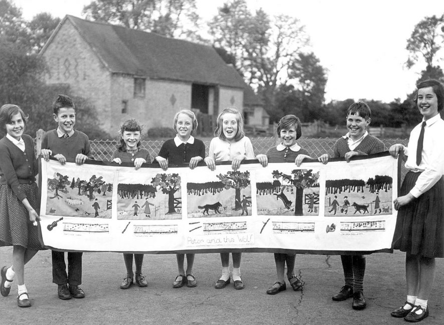 Children at Gaydon school, holding a collage of Peter and the Wolf. From left to right: Deanne Morris, Michael Olds, Celia Cowley, Caroline Brown, Joan Randall, June Sparrow, Michael Liddington and Elizabeth Duckett.  1959 |  IMAGE LOCATION: (Warwickshire County Record Office) PEOPLE IN PHOTO: Sparrow, June, Sparrow as a surname, Randall, Joan, Randall as a surname, Olds, Michael, Olds as a surname, Norris, Deanne, Norris as a surname, Liddington, Michael, Liddington as a surname, Duckett, Elizabeth, Duckett as a surname, Cowley, Celia, Cowley as a surname, Brown, Caroline, Brown as a surname