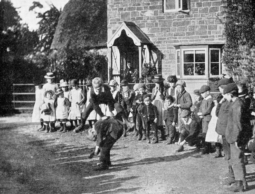 Young people at Compton Wynyates playing leapfrog.  1910s |  IMAGE LOCATION: (Warwickshire County Record Office)