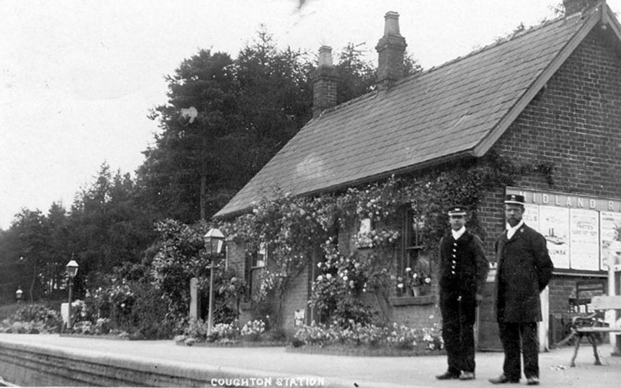 Station Master and porter standing outside the booking hall at Coughton railway station, which is bedecked with flowers.  1900s |  IMAGE LOCATION: (Warwickshire County Record Office)