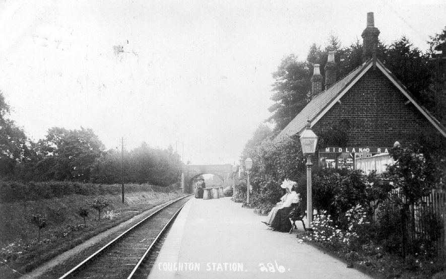 Coughton railway station with passengers and milk churns waiting for the train.  1900s |  IMAGE LOCATION: (Warwickshire County Record Office)