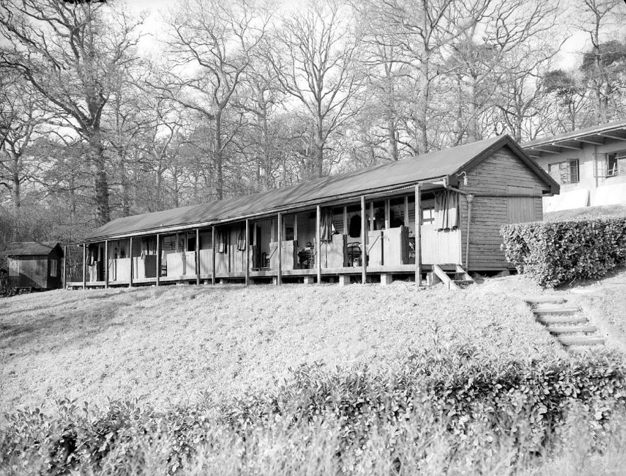 King Edward VII Memorial hospital, Hatton, exterior of probably temporary buildings.  1953 [ The 'temporary buildings' comment is unsubstantiated and misleading. The Pavilion system where treatment involved patients getting as much fresh air as possible, hence the open verandah where beds could be wheeled out.] |  IMAGE LOCATION: (Warwickshire County Record Office)